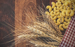 Ears of wheat and pasta. Vintage toned picture of the ears of wheat with pasta on the wooden background Royalty Free Stock Photos
