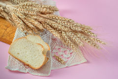 Ears of wheat and white bread rusks on a wooden board stock images