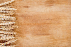 Ears of wheat on wooden background Stock Photography