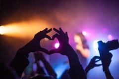 ? eart folk visar deras förälskelse, händer som lyfts upp på musikalisk konsert arkivbilder