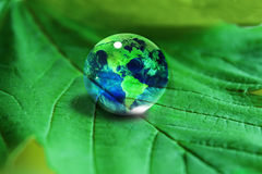 Earth. In waterdrop  on green leaf Royalty Free Stock Image