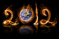 Earth 2012 year in fire. Earth in danger 2012 year fire with sparkles on black Royalty Free Stock Photos