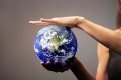 Earth. A woman holding the earth in her hands stock photography