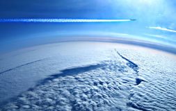 Earth from above the clouds and plane royalty free stock photo