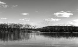 Earth Air and Water. Monochrome scenic view of the lake frome shore with bare trees and hiille on the opposite shore reflecting in the watter under partly cloudy royalty free stock image