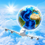 Earth with airplane against clouds and sun Royalty Free Stock Images