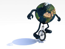 Earth with arms and legs rides a unicycle Stock Photo