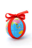 The earth as a gift. World as a gift, small world with red ribbon, selective focus, isolated on white,studio shot royalty free stock photos