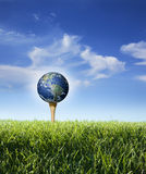 Earth as golf ball on tee with grass, blue sky. The earth on a golf tee in grass with blue sky and clouds credit to royalty free stock image