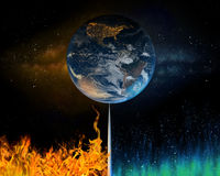 Earth balancing between fossil fuels and renewable energy. Earth balancing on a tipping point between fire of fossil fuels leading to global warming and stock image