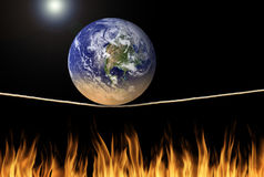 Earth balancing on tightrope over fire environmental climate change message. Earth balancing on tightrope over fire flames with the sun in background Stock Photos