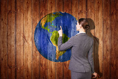 Earth ball texture on wood background. Woman stands near earth ball texture on wood background. Elements of this image furnished by NASA stock image