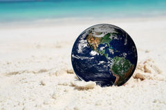 The earth on beach, including elements furnished by NASA Stock Images