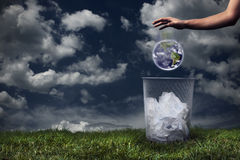 Earth being dropped in the trash Royalty Free Stock Image