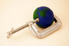 Earth being squeezed by clamp. Environmental theme Royalty Free Stock Image