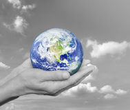 Earth in black and white hands over black and white sky with clo Stock Photos