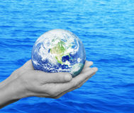 Earth in black and white hands over blue sea background, Environ Stock Photos