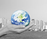 Earth in black and white hands over city tower and river backgro Stock Image