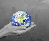 Earth in black and white hands over pollution city, Environment Stock Photos