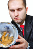 Earth and businessmen. The businessman in a suit has control over a sphere of a terrestrial planet and looks at it Royalty Free Stock Photo