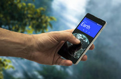 Earth Calling. An hand holding a mobile phone with a call from Earth Royalty Free Stock Photography