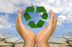 Earth care. Hands with recycle symbol over a dry soil and sky background Royalty Free Stock Photos