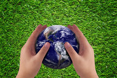 Earth Care Concept. Love and care the earth concept, hand and blue planet on green grass background, nature and ecology, Elements of this Image Furnished by NASA Royalty Free Stock Images