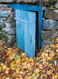 Earth cellar in the autumn. Old rustic blue door in front stock photo