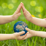 Earth in children`s hands. Against green spring background. Elements of this image furnished by NASA Royalty Free Stock Photos