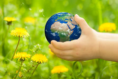 Earth in children`s hands Stock Photos