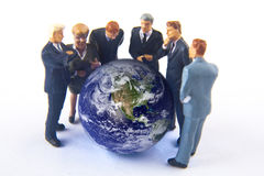 Earth Commitee. Miniature business people standing around the earth Royalty Free Stock Photography
