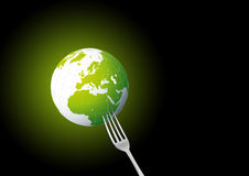 Earth consumption. Planet Earth pick on metal fork Stock Images