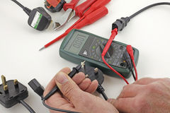 Earth continuity testing. An electrician testing a mains cable earth with a multimeter royalty free stock photo