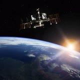 围绕Earth.3D场面旋转的空间站 库存照片