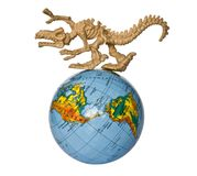 Earth in danger. Toy dino skeleton prowling around the globe Stock Images