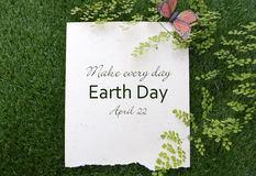 Earth Day, April 22, Concept Image. Earth Day, April 22, Concept with recycled paper in grass with fern and butterfly and text Stock Photo