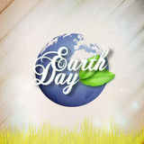 Earth Day background with the words, world globe and green leaves. Wooden texture. Vector illustration Stock Image