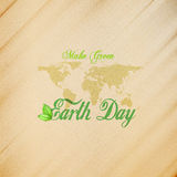 Earth Day background with the words, world map and green leaves. Wooden texture. Vector illustration Royalty Free Stock Images