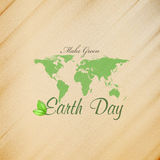 Earth Day background with the words, world map and green leaves. Wooden texture. Vector illustration Stock Images