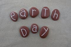 Earth day with brown carved stones over beach sand Royalty Free Stock Images