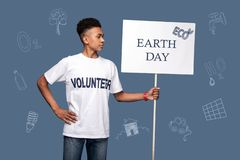 Confident volunteer being ecofriendly and celebrating Earth day. Earth day. Calm confident young man standing with a sign and feeling proud while drawing stock photo