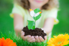 Earth day. Child holding young plant in hands against spring green background. Ecology concept. Earth day Stock Photos