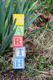 Earth Day Color wooden blocks. Earth spelled out in wooden blocks against unbloomed flowers with grass and leaves Royalty Free Stock Photos