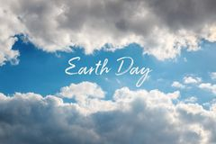 Earth Day concept card with natural frame of clouds in the sky. Natural frame of clouds in the sky with text Earth Day. April 22 concept card stock image