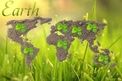 Earth Day. Concept ecology. World map, globe from the soil with green plants around the world on natural background royalty free illustration