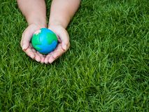 Earth day. earth in hands and green grass field background. envi stock photos