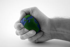 Earth day / environment series (I). Earth day / environmental motif of hand squeezing the earth with selective desaturation...metaphor is versatile royalty free stock photography