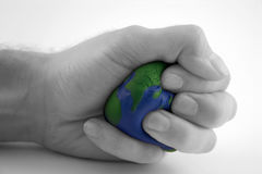 Earth day / environment series (II). Earth day / environmental motif of hand squeezing the earth with selective desaturation...metaphor is versatile Stock Photography