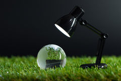 Earth day or environmental concept. Table lamp lights up crystal globe on the grass Stock Image