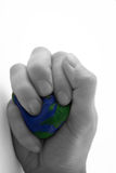 Earth day / environmentalism series (IV). Earth day / environmental motif of hand squeezing the earth with selective desaturation...metaphor is versatile Stock Photo